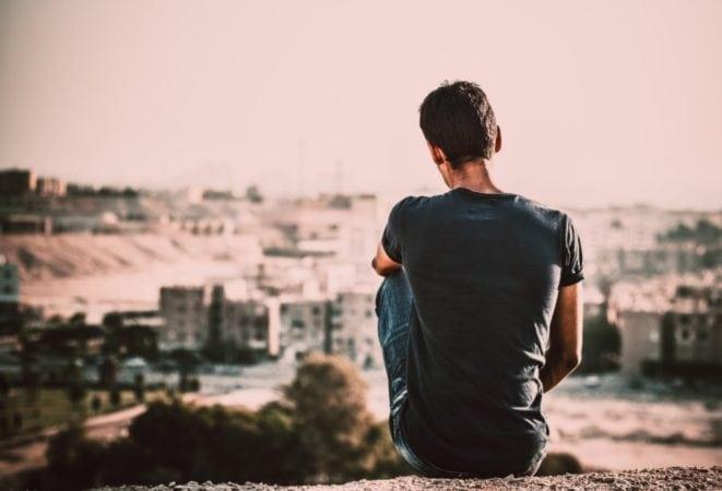 Mann, der von einem Hügel auf eine Stadt sieht