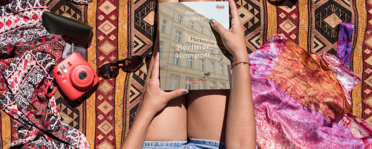 """Frau am Strand sitzend auf einer Decke in kurzer Hose hat das Buch """"Berliner Kompott"""" aus der Krimiserie mit BM Fogos auf dem Schoß liegend in den Händen. Von oben fotografiert"""