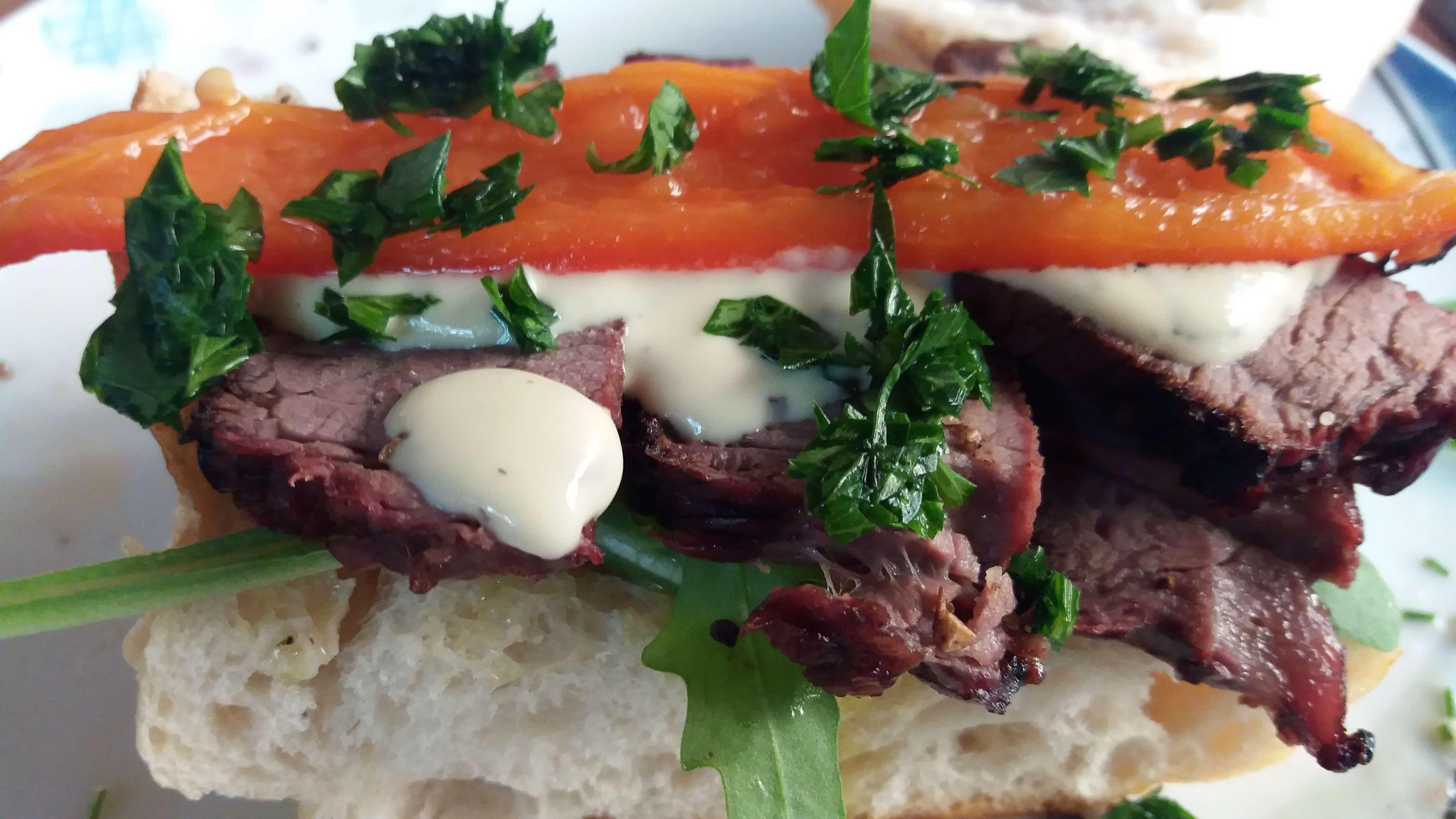 Weißbrot mit Gegrilltem auf Rucola mit Senfsoße und Paprika